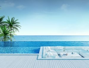 Relaxing summer beach , Sunbathing deck and private swimming pool with Palm trees near beach and panoramic sea view at luxury house /3d rendering